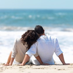 Rear view of a couple sitting on beach with woman leaning head on man's shoulder